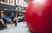 Passersby and a bus go passed Kurt Perschke's giant Red Ball that was squeezed into the entrance of