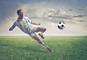 Jogador de futebol, atirando uma bola em um campo de futebol