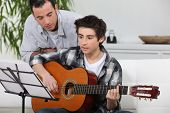 picture of fret  - Adolescent boy learning to play the guitar - JPG