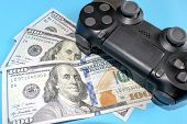 Black Game Joystick With Us Dollars On Blue Background. Playing For Money Concept. Game Pad With Mon poster