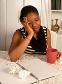 Melancholic african woman writing a letter at home