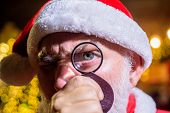 Bearded Santa Looked With Curiosity Through Magnifying Glass. Bearded Man In Santa Hat Holds Magnify poster