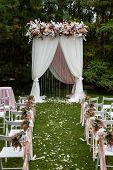 Wedding Arch Decorated With Flowers Outdoors. Beautiful Wedding Set Up. Wedding Ceremony In The Gard poster