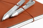 A Journal With Red Leather Cover And Elastic Band Securing Two Metallic Ballpoint Pens. poster