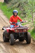 picture of four-wheel drive  - Young adult female riding a 4 wheeler on a dirt road - JPG