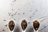 Different Varieties Of Tea Leaves In White Measuring Spoons On A White Textured Background. Three Sp poster