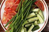 stock photo of risque  - Tomatoes cucumbers and a green onions on a plate - JPG
