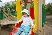 Cute Little Girl Wearing White Blouse Prepares For Rolling At Slide In Playground
