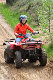 picture of four-wheel  - Young adult female riding a 4 wheeler on a dirt road - JPG