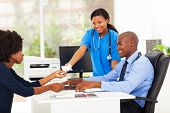 caring nurse handover tissue to sick patient in doctor's office