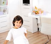 Portrait of little boy wearing white t-shirt and standing for posing at his room at home