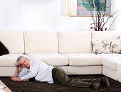 Elderly man having heart attack lying on floor at home
