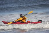 Man Fighting The Wave On Kayak  On Rough Sea