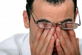 stock photo of fatigue  - Tired man rubbing his eyes - JPG