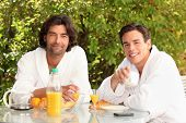 45 years old man and a 20 years old man dressed in bathrobe drinking coffee at breakfast