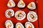 Japanese Cuisine : Sushi Maki Roll with Vegetables and Salmon inside . on red dish with sticks isola