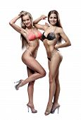 Two Beautiful Athletic Girl Wearing Bikini Posing Over White Background