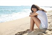 stock photo of sorrow  - Portrait of a worried girl sitting on the beach with the sea in the background - JPG