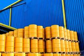 stock photo of fuel economy  - Yellow oil drums in front of a factory with blue cladding - JPG