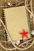 Exercise book and sea stars on sand