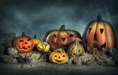 image of funny ghost  - Halloween pumpkins on a wooden desk at night - JPG