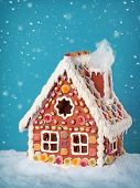 stock photo of gingerbread house  - Homemade gingerbread house on blue background - JPG