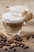 Glass of cappuccino with heart cookie