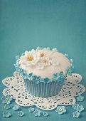 Cupcake with white and blue flowers on blue background