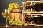 Wooden case with wine bottle, barrel, wineglass and grape on wooden table on grey background