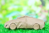 Car wrapped in brown kraft paper, on green grass, on nature background