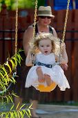 Toddler Girl On The Swing Pushed By Her Grandmother