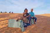 Unidentified Vietnamese Young Boys With Sandboards For Tourists On Red Sand Dunes. Mui Ne. Vietnam