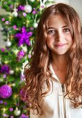 Closeup portrait of sweet teen girl on Christmas tree background, New Year children's party, happy wintertime holidays concept