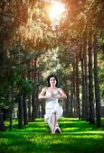 image of virabhadrasana  - Yoga virabhadrasana I warrior pose by woman in white costume on green grass in the park around pine trees - JPG
