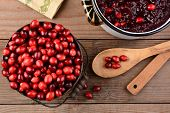 Overhead of a bucket of cranberries and a pot full of whole cranberry sauce on a rustic wooden table