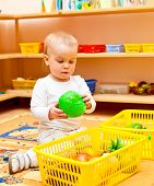 Little baby girl playing with toys at nursery