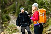 Couple Happy Hikers Walking In Mountains