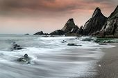 Landscape Seascape Of Jagged And Rugged Rocks On Coastline With Long Exposure Motion Blur