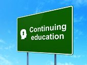 Education concept: Continuing Education and Head With Keyhole on road sign background