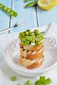 Toasted bread topped  (Bruschetta) with green peas and ricotta cheese