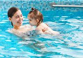 One Year Baby Girl At Her First Swimming Lesson With Mother