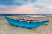 Traditional Sri Lankan fishing boat on empty sandy beach at sunset.