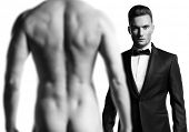 Stylish man in black suit in front of nude athletic male model