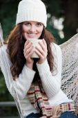 stock photo of beautiful brunette woman  - A portrait of a beautiful teenager outdoor drinking coffee - JPG