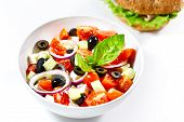 Light Greek Salad With Fresh Vegetables And Burger In The Background. On White.