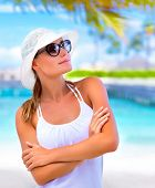 Closeup portrait of cute blond girl enjoying summer day on the beach, wearing white hat and stylish sunglasses, vacation concept