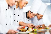 Asian Indonesian chef along with other cooks in restaurant or hotel kitchen cooking, finishing dish