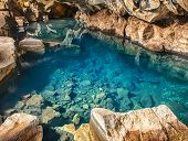 foto of incredible  - Volcanic cave Grjotagja with a incredibly blue and hot thermal water near lake Myvatn in the northeastern Iceland - JPG