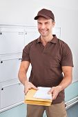 foto of postman  - Portrait Of Happy Mature Postman Holding Letters - JPG