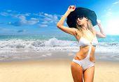 Beautiful young woman in bikini with black strw hat on the beach